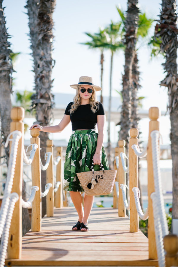 Jessica Sturdy pairing a palm leaf skirt and straw tote with a boater hat.