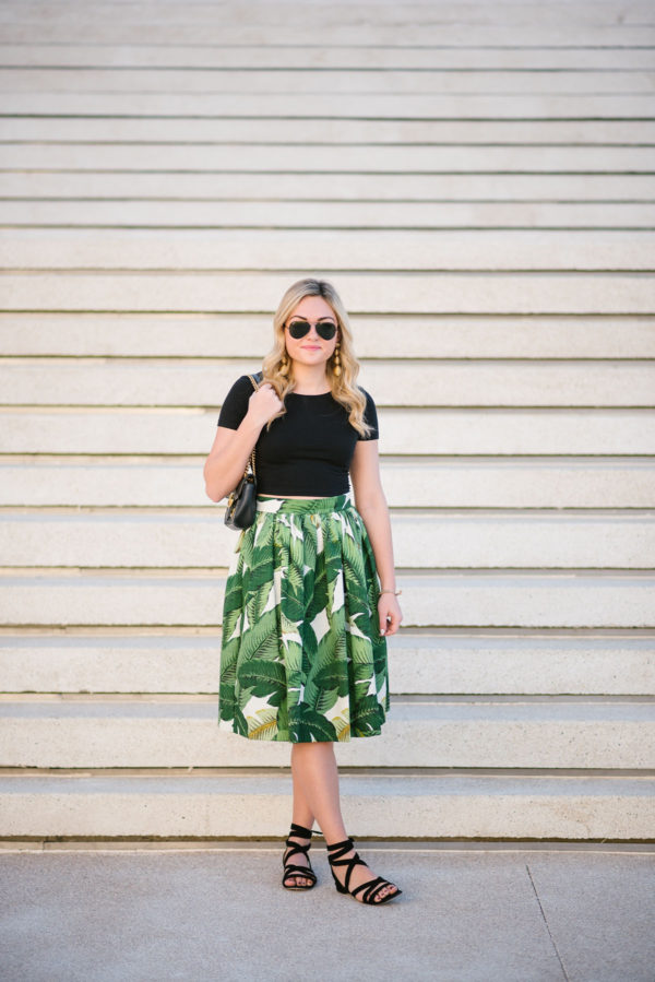 Travel writer Bows & Sequins wearing a M.Gemi lace-up sandals, a black tee, and a palm leaf midi.