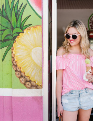 Lifestyle blogger Bows & Sequins wearing a Vineyard Vines blouse and Amuse Society cut off jean shorts.