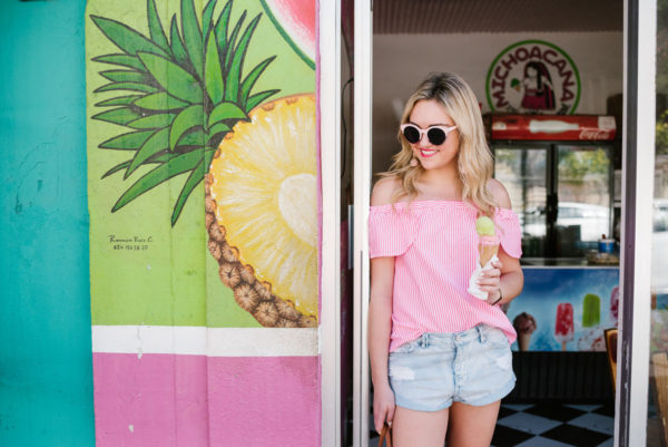 Lifestyle blogger Bows & Sequins wearing a Vineyard Vines off-the-shoulder striped blouse and Amuse Society cut off jean shorts.