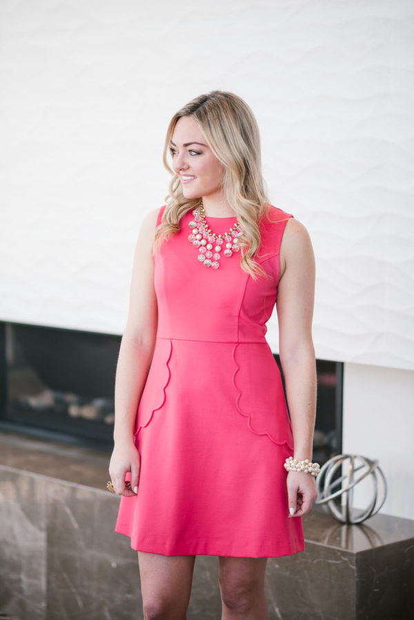 Bows & Sequins waring a pink dress with a statement necklace.
