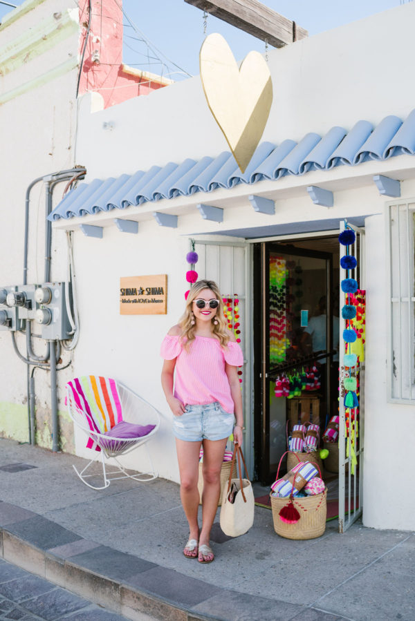 Fashion blogger Bows & Sequins wearing a pink off the shoulder blouse and Amuse Society jean shorts with Jack Rogers in downtown San Jose del Cabo.