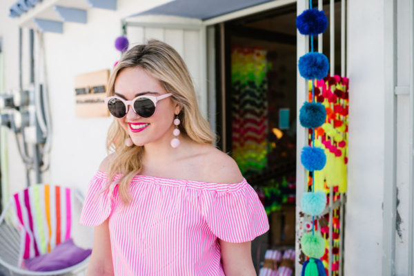 Lifestyle blogger Bows & Sequins styling pink Baublebar earrings and a pink off the shoulder blouse in front of colorful pom-pom store in downtown San Jose del Cabo Mexico.