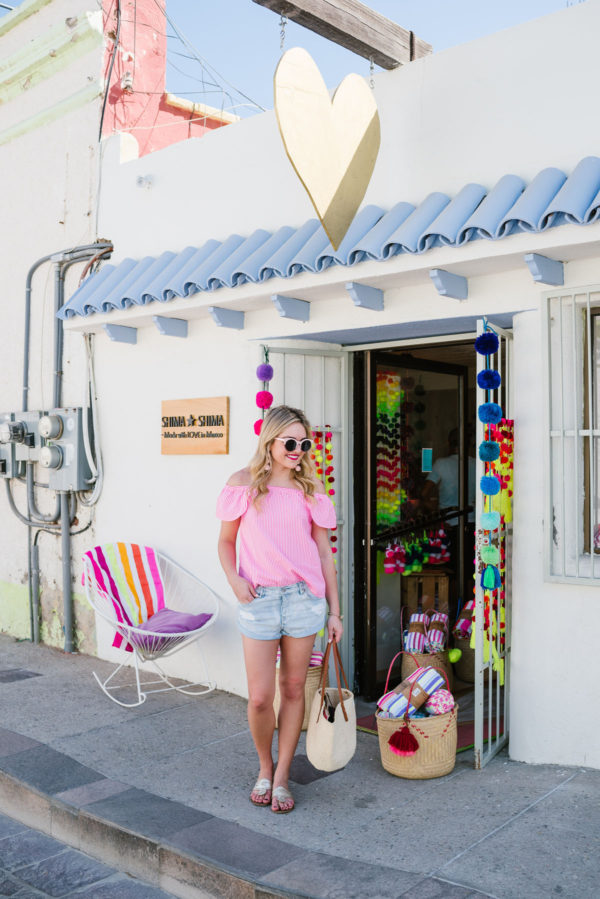 Bows & Sequins wearing a pink blouse with jean shorts, Jack Rogers, and a Clare V Kenya tote in downtown Cabo Mexico. Shima Shima is a must-shop in San Jose del Cabo!