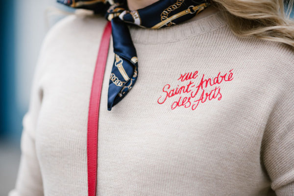 Bows & Sequins wearing a cashmere Maje sweater with red embroidery reading Rue Saint Andre des Arts.