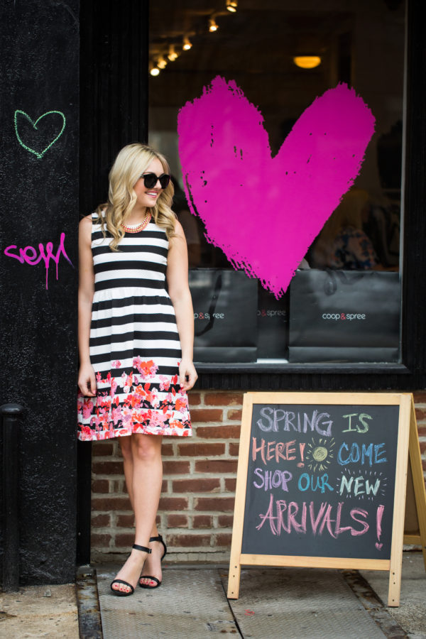 Bows & Sequins wearing a black and white striped dress with a floral pattern.