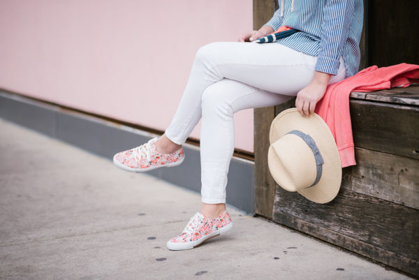 Bows & Sequins sharing a spring outfit idea: white jeans, a striped shirt, and floral sneakers.