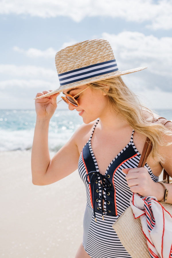 Bows & Sequins wearing a navy striped swimsuit with orange piping and a Hat Attack x Lemon Stripes navy striped straw sunhat.