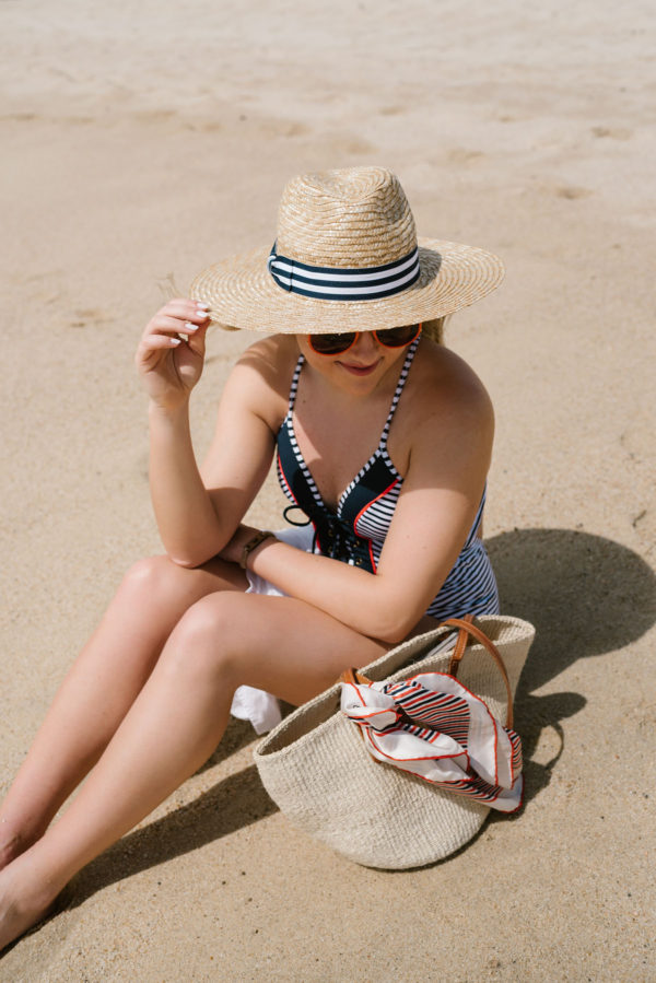 Bows & Sequins wearing a navy striped sunhat with a Clare V straw tote on the beach in Cabo.