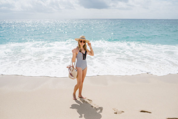 Travel blogger Bows & Sequins by the ocean in Mexico wearing a blue and white striped swimsuit with a straw hate and straw beach bag.