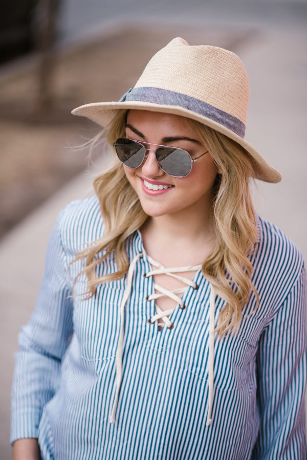 Bows & Sequins styling a blue and white striped shirt with mirrored aviators and a straw hat.