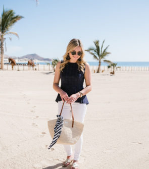 Fashion blogger wearing a blue peplum top with a Clare V straw tote in Cabo San Lucas, Mexico.