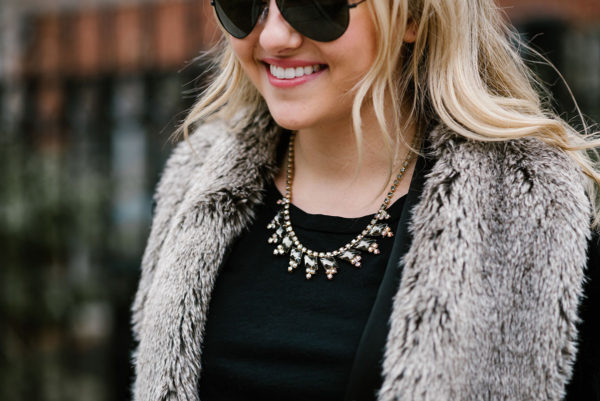 Bows & Sequins wearing a statement necklace from Sweet & Spark with a faux fur vest.
