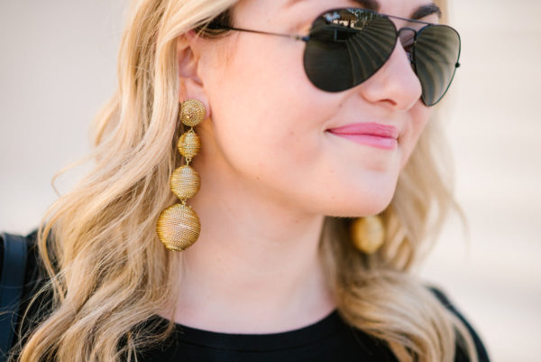 Fashion blogger Bows & Sequins wearing gold Tuckernuck earrings and Ray-Ban black aviators.