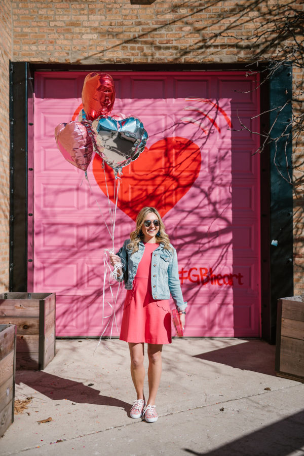 Bows & Sequins styling a pink dress in front of the Pink and Red Heart Garage Door in Chicago.