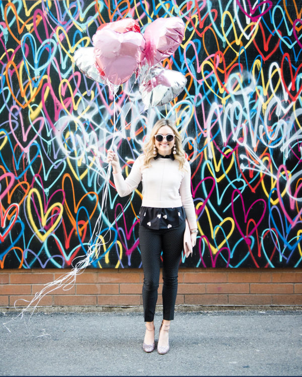 Bows & Sequins styling Valentine's Day outfits in Chicago in front of the Bleeding Hearts mural in Chicago.