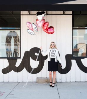 Bows & Sequins wearing a black and white outfit for Valentine's Day in Chicago with balloons.