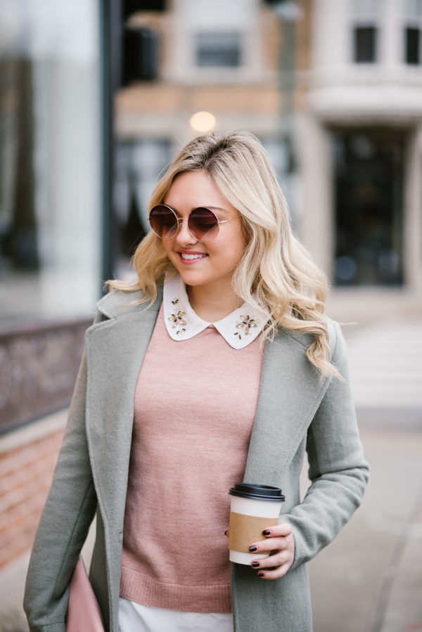 Lifestyle blogger wearing mint green coat with blush pink clutch.