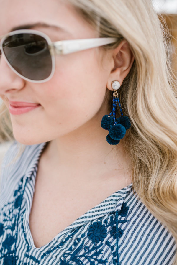 Bows & Sequins styling white Coach sunglasses with blue statement earrings.