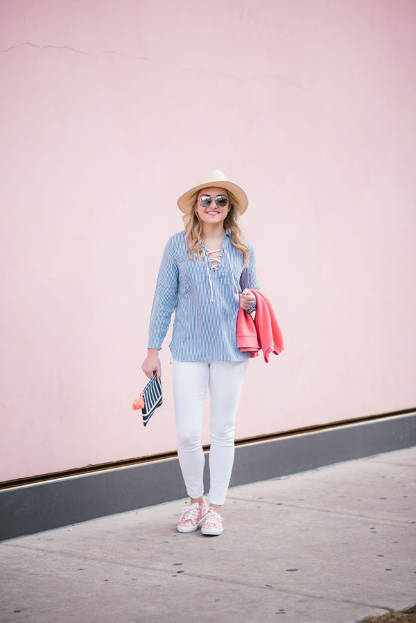 Bows & Sequins wearing a straw hat, striped blue and white shirt, white jeans, and printed sneakers for a fun spring outfit!