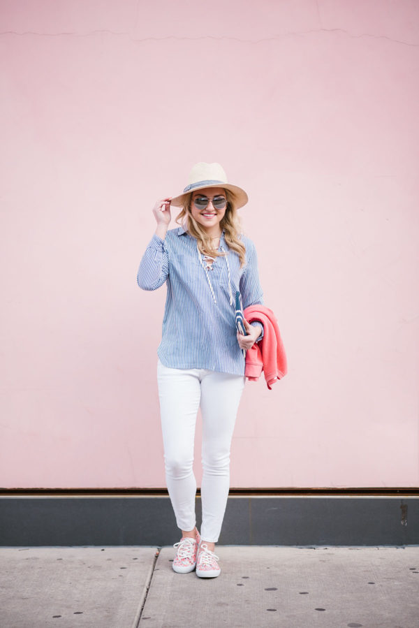 Bows & Sequins wearing a spring outfit on the blog: straw hat, long-sleeved striped top, white jeans, and floral printed sneakers.