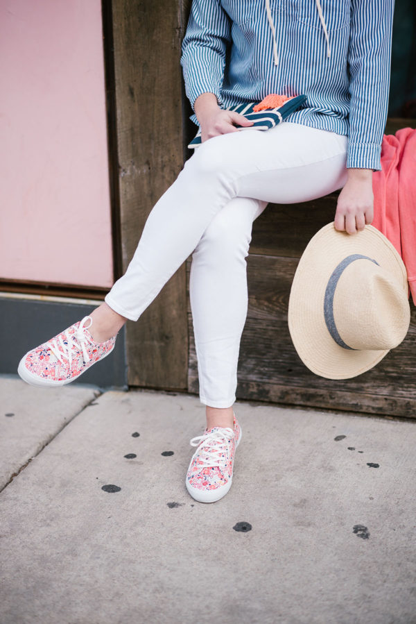 Bows & Sequins wearing white jeans from Old Navy with printed floral sneakers and a Hat Attack straw hat for spring.