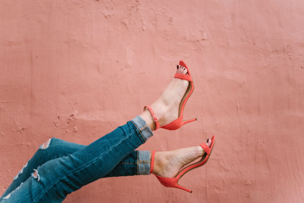 Fashion blogger Bows & Sequins wearing coral ankle strap sandals and cuffed skinny jeans against a pink wall in Chicago.