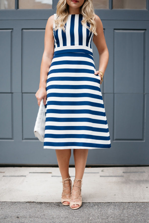 Bows & Sequins wearing a blue and white striped dress with nude heels and a white clutch.