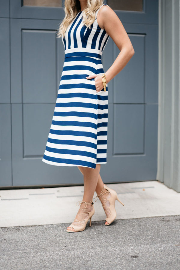 Bows & Sequins wearing a blue and white striped dress with nude lace-up heels.