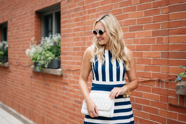 Bows & Sequins styling a blue and white striped dress with a white leather clutch and white sunglasses.