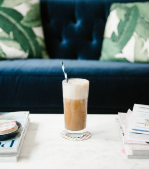 Bows & Sequins sharing a recipe to make iced almond lattes at home. A glass of iced coffee sitting on a marble coffee table with a navy velvet tufted sofa and palm leaf pillows in the background.