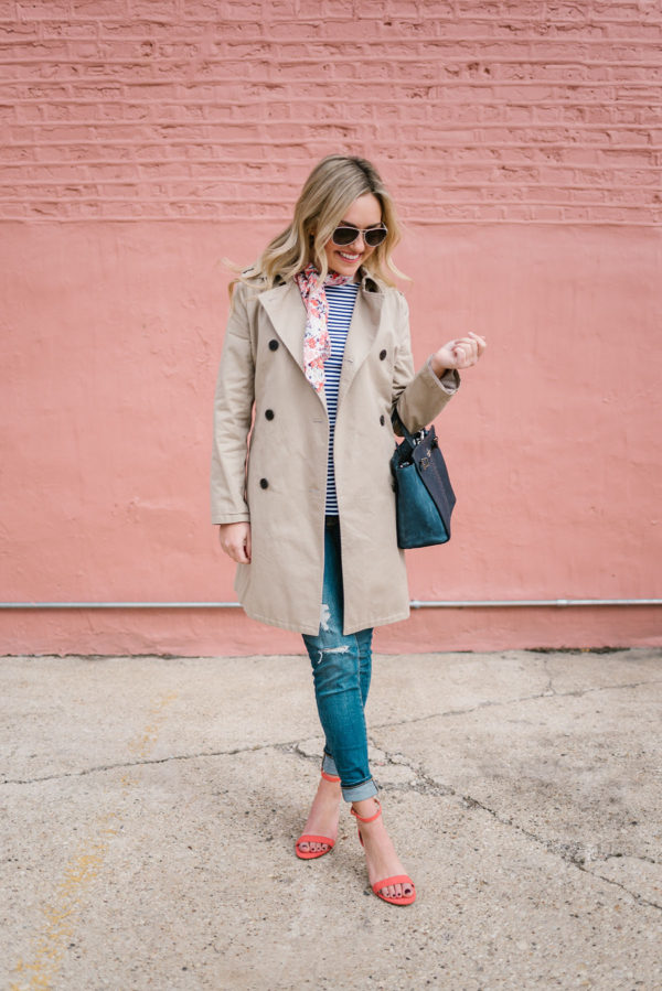 Jessica from Bows & Sequins wearing a tan trench coat with a navy Kate Spade bag, distressed denim, and coral heels.