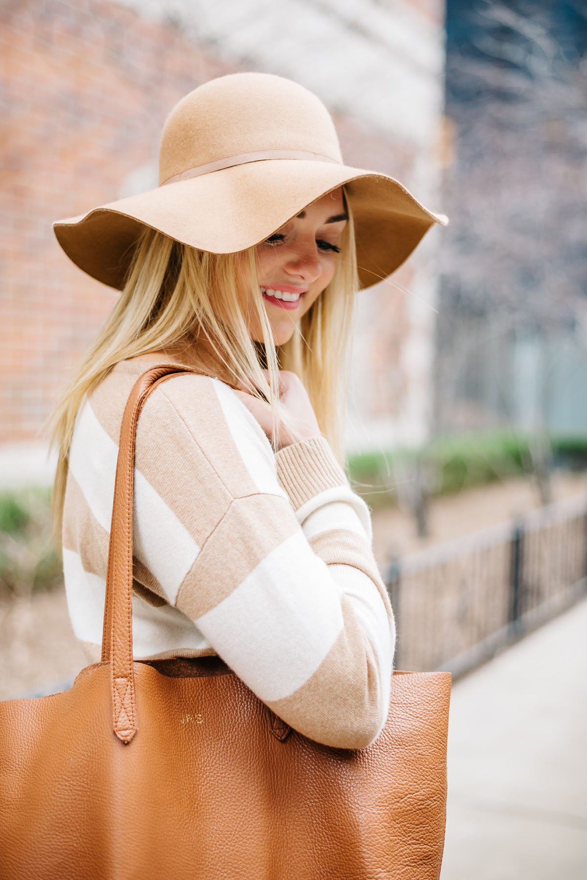Bows & Sequins wearing a camel hat, striped sweater, and monogrammed leather Cuyana tote.