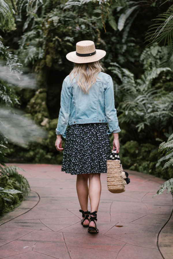 Bows & Sequins styling a floral print dress with a straw tote, sun hat, and lace up sandals in Chicago.