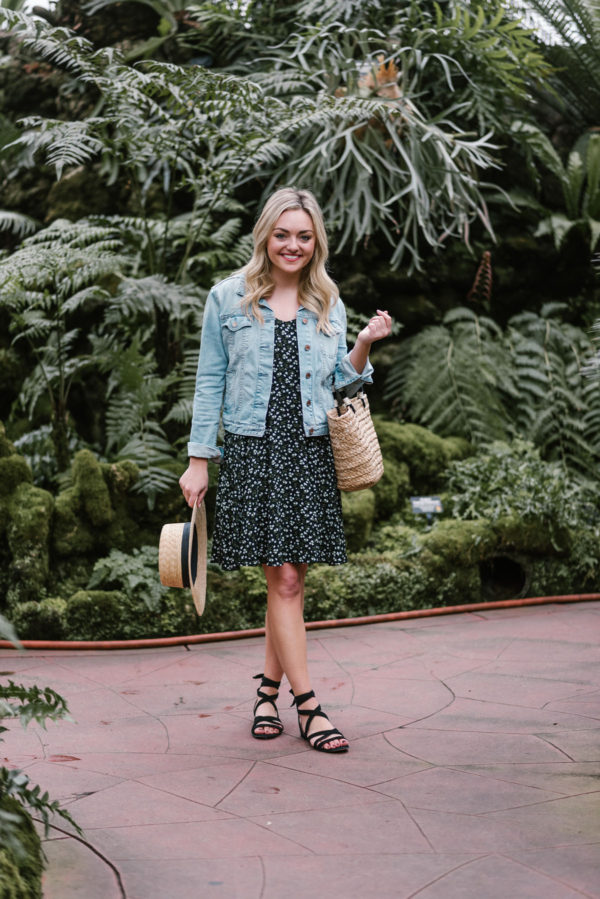 Lifestyle blogger Bows & Sequins wearing a floral dress with a light denim jacket and straw accessories for spring.