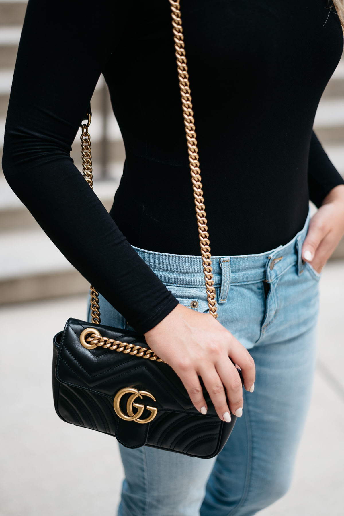 Bows & Sequins accessorizing a black bodysuit with a leather Gucci gold chain bag.