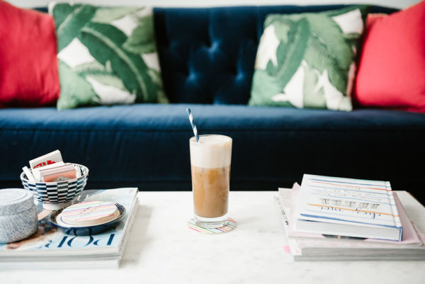 Bows & Sequins sharing a recipe to make iced almond lattes at home. A glass of iced coffee sitting on a marble coffee table with a navy velvet tufted sofa and palm leaf and hot pink pillows in the background.