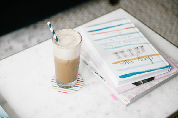 Bows & Sequins sharing an iced almond milk latte recipe. An iced latte in a clear glass with a blue striped straw with Chez Moi coffee table book.