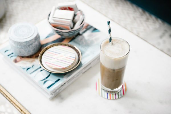 Bows & Sequins teaches how to make an iced almond milk latte. Iced glass with a navy blue striped straw on a colorful striped coaster with a stack of magazines.