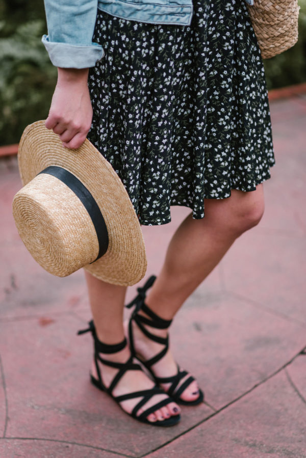 Bows & Sequins accessorizing a floral printed Old Navy dress with a straw hat and black lace up M. Gemi sandals.