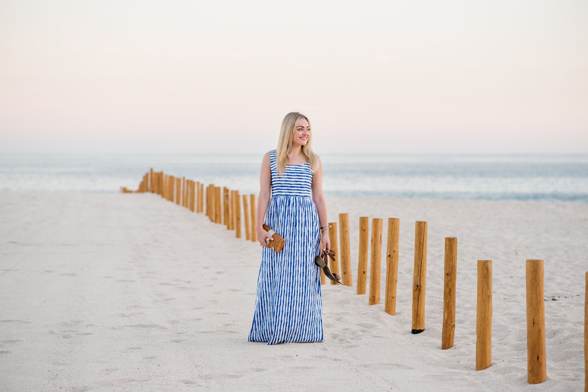 Travel blogger Bows & Sequins wearing a blue striped maxi dress on the beach in Cabo, Mexico.