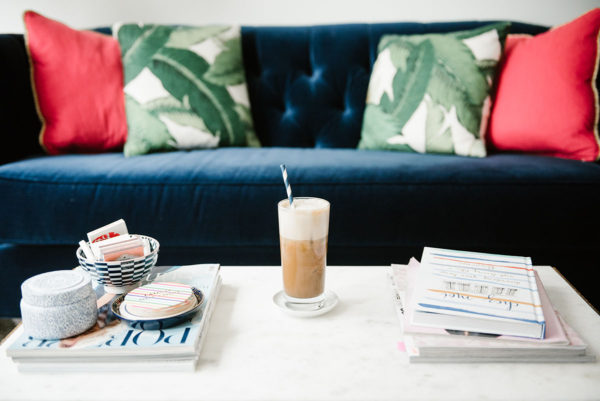 Bows & Sequins sharing a recipe to make iced almond lattes at home. A glass of iced coffee sitting on a marble coffee table with stacks of magazines and coffee table books, with a navy velvet tufted sofa and palm leaf pillows in the background.