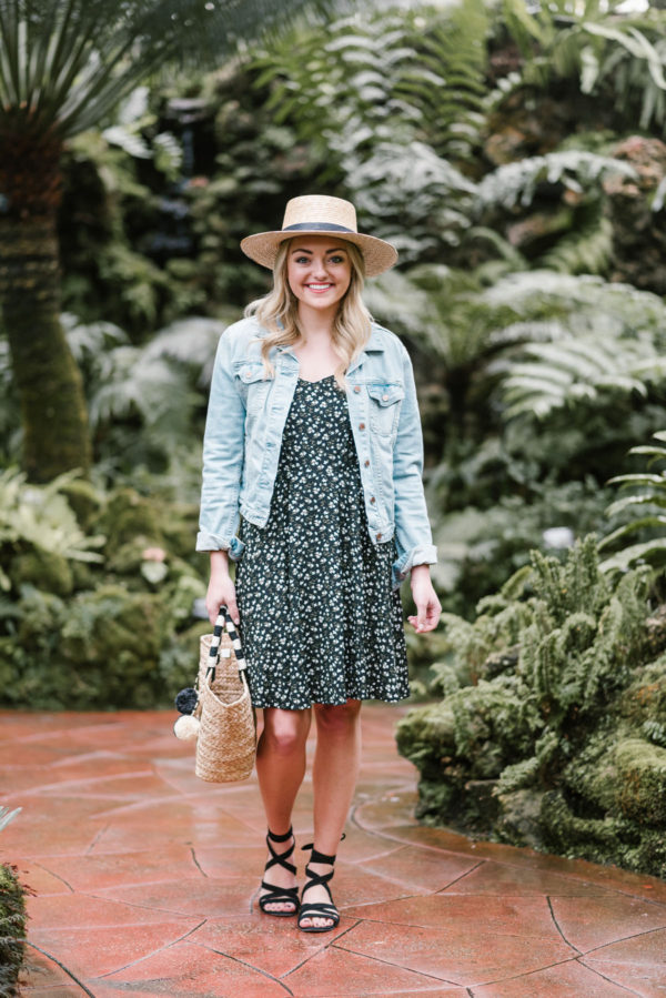 Fashion blogger Bows & Sequins wearing a floral sundress with a Janessa Leone straw hat and a pom pom tote.