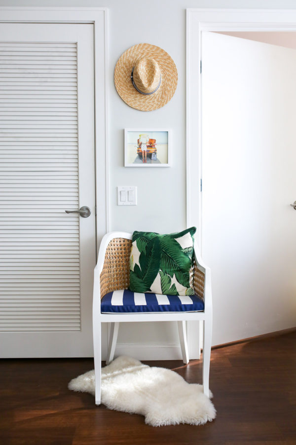 Bows & Sequins living room decor in Chicago: rattan chair with blue and white striped cushion, palm leaf print pillow, a sheepskin rug, and a straw hat hanging on the wall.