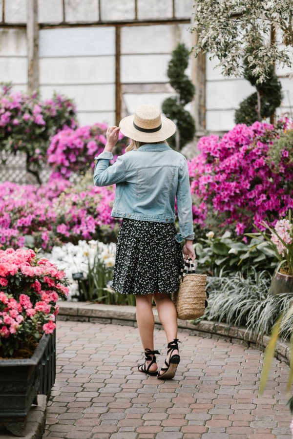 Lifestyle blogger Bows & Sequins accessorizing a floral Old Navy dress with black lace-up sandals and a straw hat.