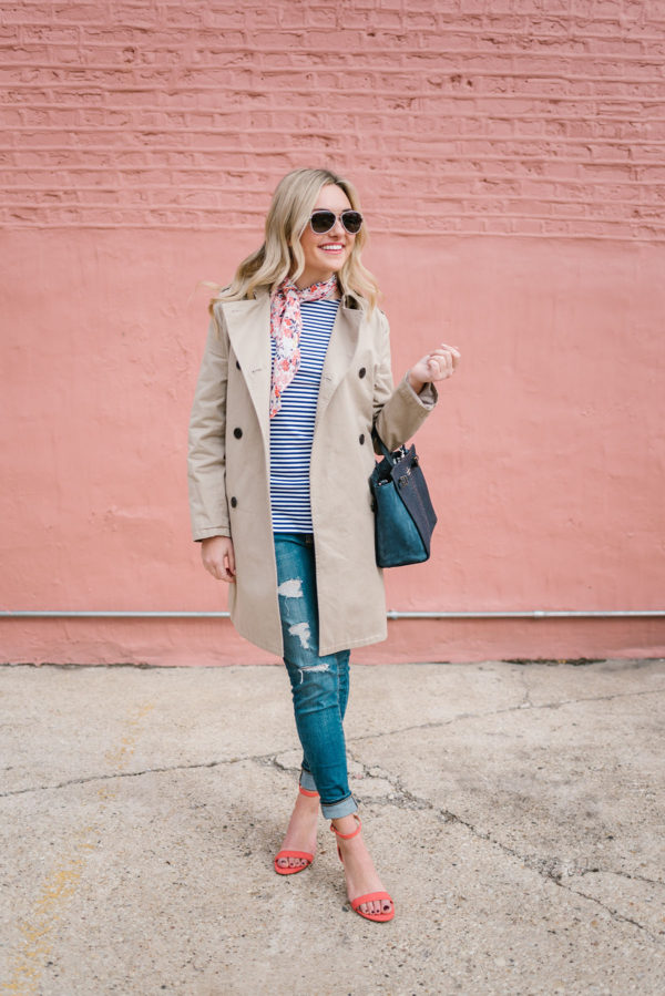 Bows & Sequins styling a women's trench coat with a navy Kate Spade bag and distressed skinny jeans.