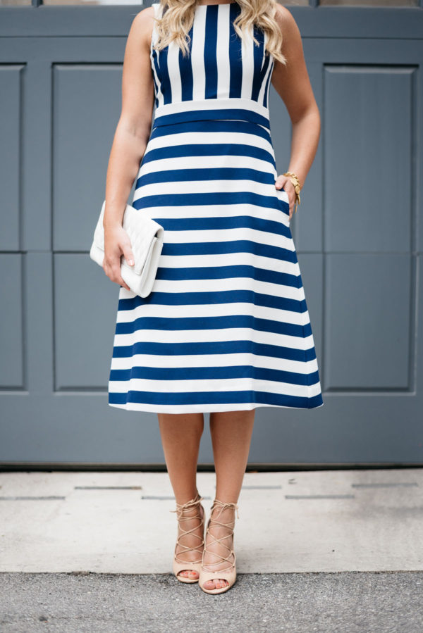 Bows & Sequins wearing a blue and white striped dress with nude heels.