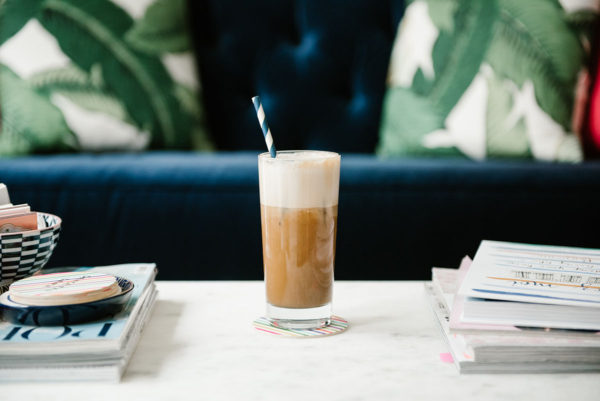 Bows & Sequins shares a recipe for how to make an iced almond milk latte at home. Photographed in her living room in front of a navy blue velvet sofa on a white marble coffee table with banana leaf printed pillows.