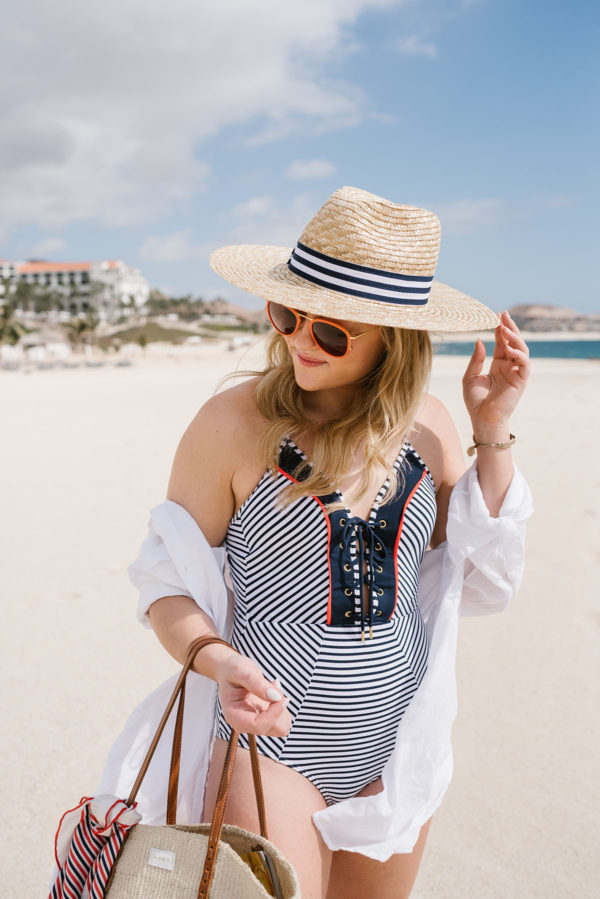 Travel blogger Bows & Sequins wearing a navy striped one-piece swimsuit with a white Azura coverup with a striped Hat Attack sunhat and orange sunglasses.