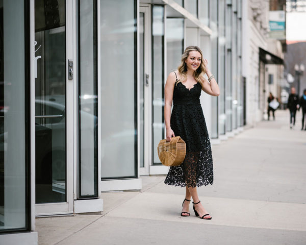 Bows & Sequins wearing a black lace dress with ankle strap heels and a bamboo bag.